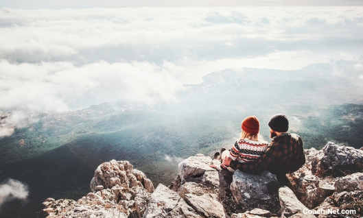 Couple Sitting On Mountain